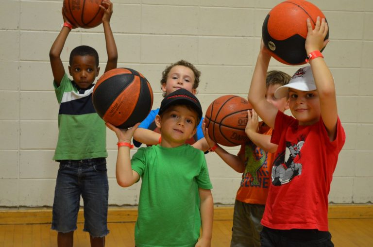 Enfants qui jouent au basketball au camp Multisports