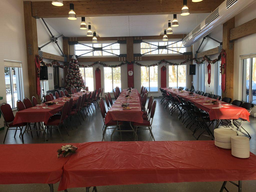 Salle communautaire montée avec tables et chaises à Noël