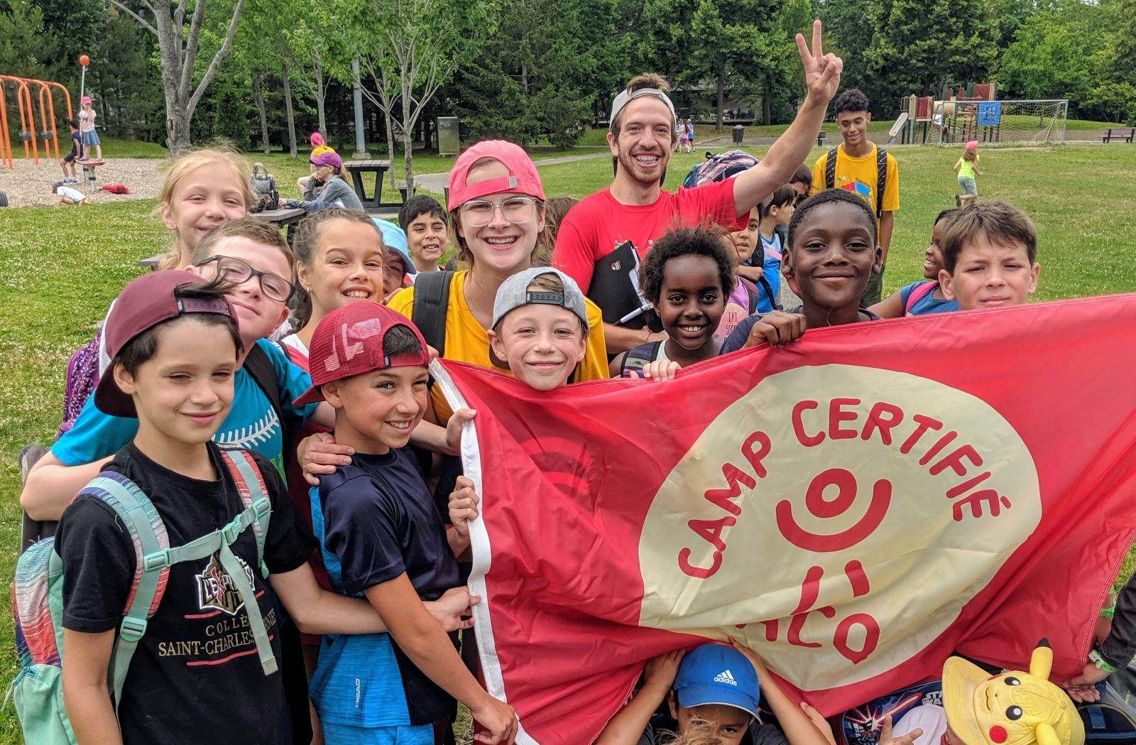 Groupe d'enfants et de moniteurs avec le drapeau de l'ACQ