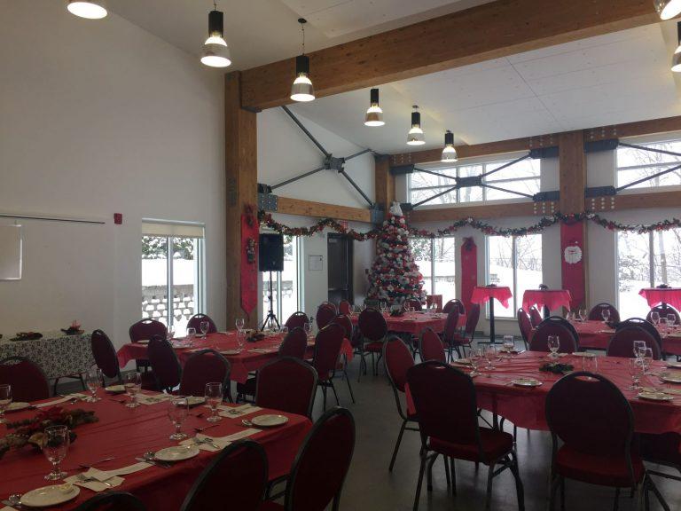 Salle communautaire montée avec les tables dans le temps de Noël